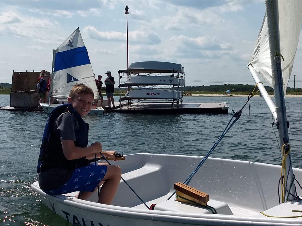 kid sailing a pram past the dock